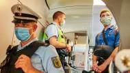 Beamte der Bundespolizei und Mitarbeiter der DB Sicherheit stehen in einem IC kurz vor dem Berliner Hauptbahnhof und kontrollieren, ob die coronabedingte Maskenpflicht eingehalten wird.