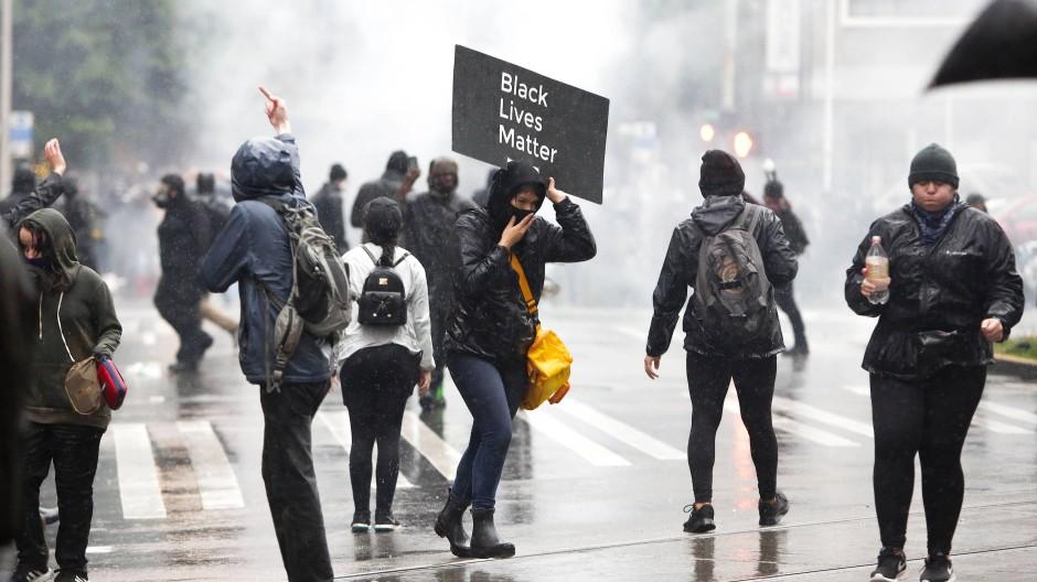 Demonstranten in Seattle fliehen am Samstag vor Tränengaswolken der Polizei.