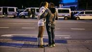 Nach den Demonstrationen in Chemnitz am Samstagabend küsst sich ein Paar vor dem Karl-Marx-Monument. Im Hintergrund überwacht die Polizei das Geschehen.