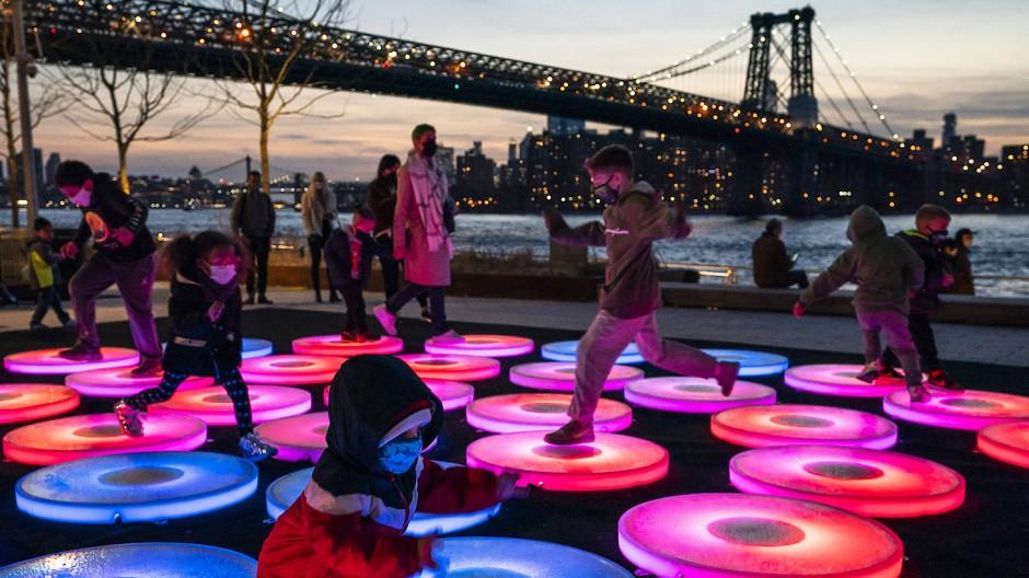 Kinder spielen auf der Kunstinstallation «Reflect» des Künstlers Jen Lewin im Domino Park im Stadtteil Brooklyn in der Nähe der New Yorker Manhattan Bridge.