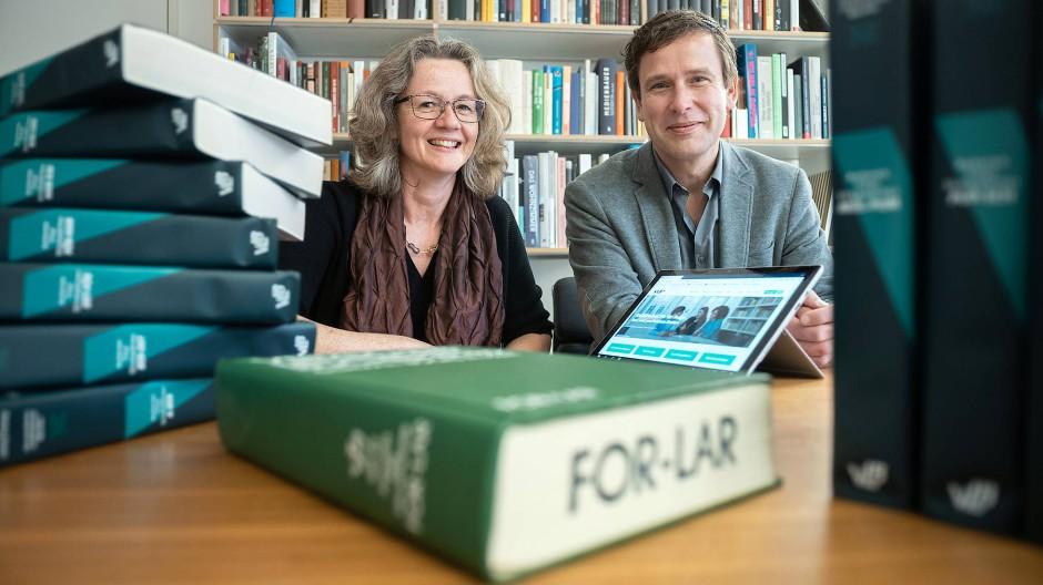 Datenerfasser: Ronald Schild und Monica Wellmann mit einer älteren Ausgabe des Bücherverzeichnisses