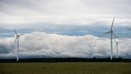 Hinter Windrädern in Niedersachsen ziehen Quellwolken auf.