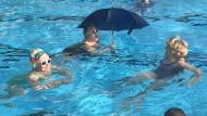 Ein bisschen Show muss doch sein: Schwimmen mit Regenschirm und Sonnenbrille bei Wind und Wetter