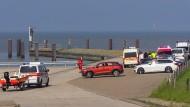 Helfer der Deutschen Lebens-Rettungs-Gesellschaft stehen bei der Suchaktion nach dem abgestürzten Kleinflugzeug auf einem Parkplatz an der Nordsee.