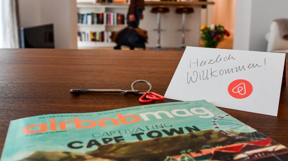 Ein Schlüssel mit einem Airbnb-Anhäger, ein Airbnbmag-Magazin und eine Herzlich-Willkommen-Karte liegen in der Wohnung eines Airbnb-Gastgebers.