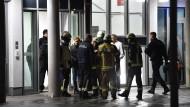 Feuerwehrleute, Polizisten und medizinisches Personal stehen vor der privaten Schlosspark-Klinik, in der Fritz von Weizsäcker während eines Vortrags erstochen wurde.