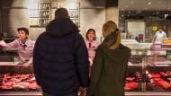 Kunden kaufen Wurst an der Fleisch- und Wursttheke in einer Edeka-Filiale.