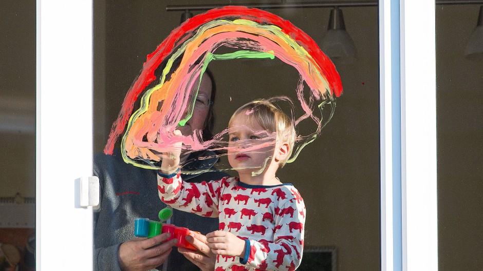 Ein Kind malt einen Regenbogen an ein Fenster.