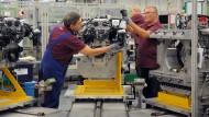 Daimler-Mitarbeiter montieren im Werk in Untertürkheim einen Motor.