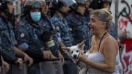 Eine Teilnehmerin eines regierungskritischen Protestes hält ihren Hund, während sie vor einer Kette Polizisten steht.