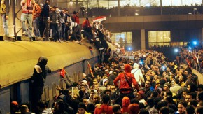 People gather around a train as they wait for the arrival of those wounded during clashes in Port Said stadium, at Ramses metro station in Cairo