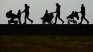 Drei Mütter schieben in Oberhomberg (Baden-Württemberg) ihre Kinderwagen eine Landstraße entlang.