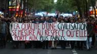"""In Paris demonstrieren Menschen im May 2019 mit einem Banner mit der Aufschrift """"Die Qualität der Zivilisation wird am Respekt gegenüber der Schwächsten gemessen""""."""