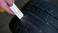 Ein Kfz-Mechaniker misst die geringe Profiltiefe eines abgefahrenen Reifens in einer Autowerkstatt