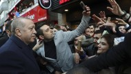 Ein Mann macht mit seinem Handy ein Selfie-Foto von sich und dem türkischen Präsidenten