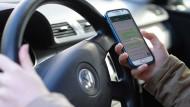Abgelenkt: Der Griff zum Smartphone während der Fahrt führt zu vielen tödlichen Unfällen.
