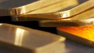 Goldbarren (100 Gramm) liegen auf einem Tisch.