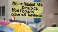 """Russlanddeutsche demonstrieren zweisprachig für eine """"sichere Heimat"""" und gegen Flüchtlinge, die das Asylrecht missbrauchen."""