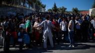 Auf Lesbos warten Migranten aus dem Moria Camp auf einen Bus, der sie aufs Festland bringen soll. Die Lager dort sind überfüllt.