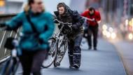 Durch den Sturm kämpfen: Fahrradfahrer in Rotterdam hält es nicht mehr auf den Rädern.
