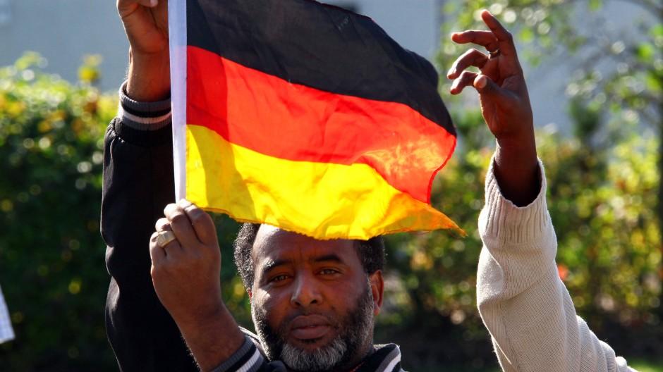 Asylbewerber halten in der Zentralen Aufnahmeeinrichtung des Landes für Flüchtlinge in Nostorf/Horst bei Boizenburg (Landkreis Ludwigslust) eine Deutschlandfahne hoch.