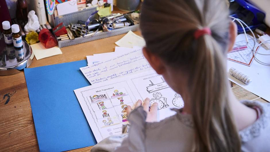 Allein, allein: Eine Schülerin der 3. Klasse arbeitet zu Hause am Schreibtisch.