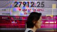 """Eine Frau geht an einer Anzeigetafel mit dem Stand des Hongkonger Aktienindexes """"Hang Seng"""" vorbei."""