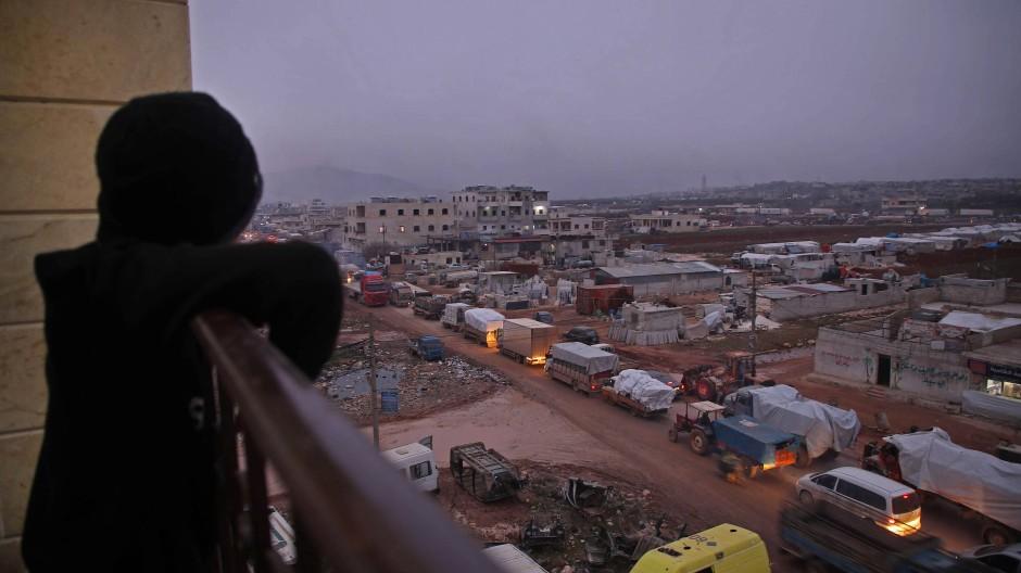 Ein Kind in der syrischen Stadt Dana beobachtet von einem Balkon, wie Autos mit Flüchtlingen in Richtung der nahen Grenze zur Türkei fahren.