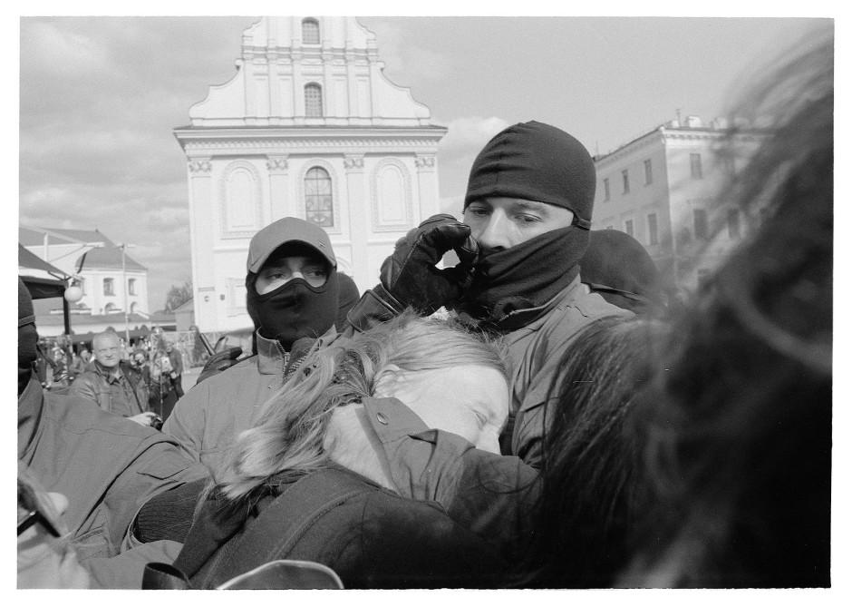 Maskiert wie ein Bandit: Ein Sonderpolizist malträtiert eine Frau.