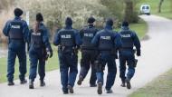 Auf Spurensuche: Polizisten durchkämmen nach dem Fund der zwei Leichen einen Park in Frankfurt am Main.