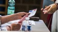 Eine Frau erhält in einem Wahllokal in Straßburg ihre Stimmzettel für die Europawahl.