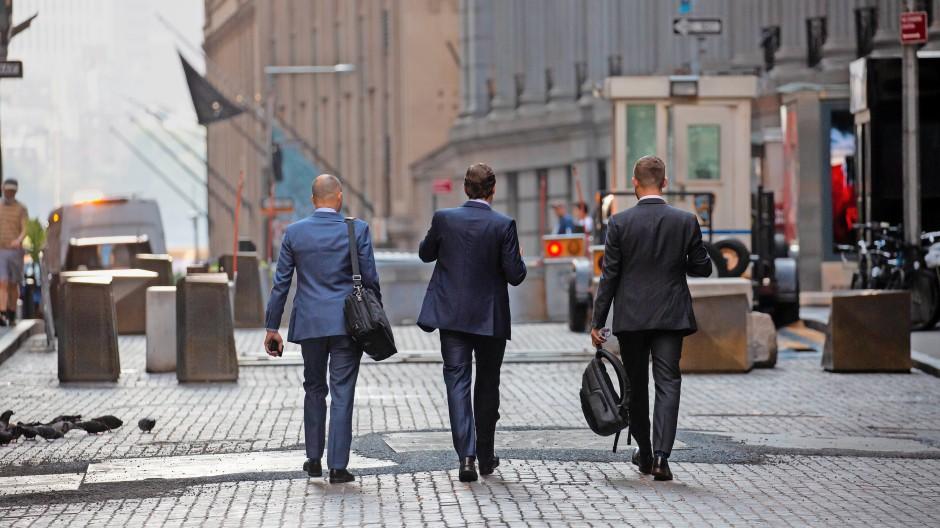 Spazieren entlang der Wall Street: New Yorks junge Banker erhalten neuerdings ein höheres Einstiegsgehalt.
