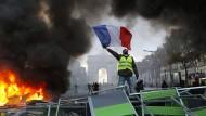 """""""Gelbwesten""""-Demonstrant auf einer brennenden Barrikade in Paris: Für das Wochenende wurden neue Demonstrationen."""