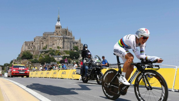 Omega Pharma-Quick Step team rider Martin of Germany cycles past the Mont Saint-Michel during the 32 km individual time trial eleventh stage of the centenary Tour de France cycling race from Avranches to Mont-Saint-Michel