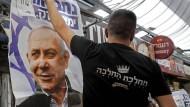 Anhänger von Ministerpräsident Benjamin Netanjahu hängen im Machane-Markt in Jerusalem Wahlplakate auf.