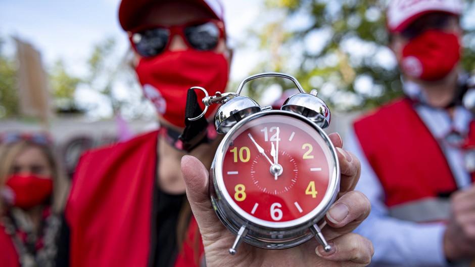 Vor der zweiten Tarifrunde im öffentlichen Dienst hält ein Demonstrant in Potsdam einen Wecker, auf dem die Zeiger auf fünf vor zwölf stehen.