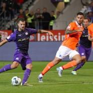 Osnabrücks Torschütze Kevin Wolze (l) erzielt den Treffer zum 2:0 gegen Dario Dumic (2.v.l) und Immanuel Höhn (r) aus Darmstadt
