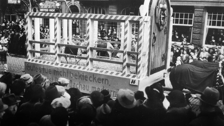 """Humor auf Kosten der Verfolgten: Wer sich zu laut beschwert, darf bald """"in Dachau meckern"""", wie ein Wagen auf dem Rosenmontagsumzug 1936 klarmacht."""