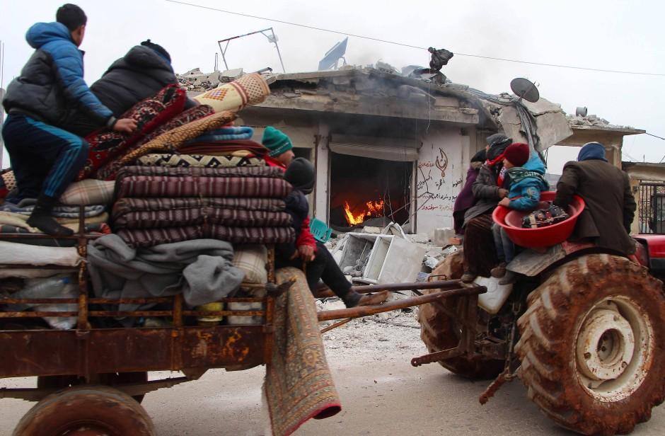 Flüchtlinge fahren mit ihrem Traktor an einem brennenden Haus in dem Ort Abian zwischen Aleppo und Idlib vorbei, der von Regimetruppen angegriffen wurde.
