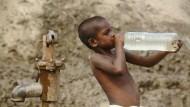 Ein kleiner Junge trinkt bei seiner Arbeit in einer indischen Ziegelstein-Fabrik: Extreme Armut zwingt viele Familien dazu, ihre Kinder zur Arbeit zu schicken.