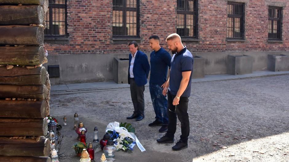 Die Rapper Farid Bang und Kollegah stehen bei der Niederlegung eines Blumengebindes an der Todeswand in der KZ-Gedenkstätte Auschwitz.