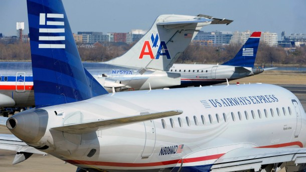 An American Airlines plane is seen between two US Airways Express planes at the Ronald Reagan Washington National Airport in Virginia
