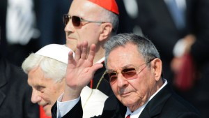 Cuba's President Raul Castro waves to the crowd while walking with Pope Benedict XVI and Vatican's secretary of state, Cardinal Tarcisio Bertone, after their arrival in Santiago de Cuba