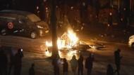 Schaulustige filmen in der niederländischen Stadt Haarlem mit Handys brennende Gegenstände, die Randalierer am 26. Januar in Brand gesetzt haben.
