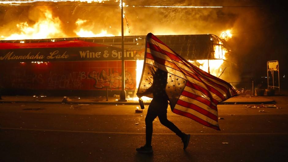Im Namen der Vereinigten Staaten: Ein Demonstrant vor einem in Brand gesteckten Alkoholgeschäft in Minneapolis.