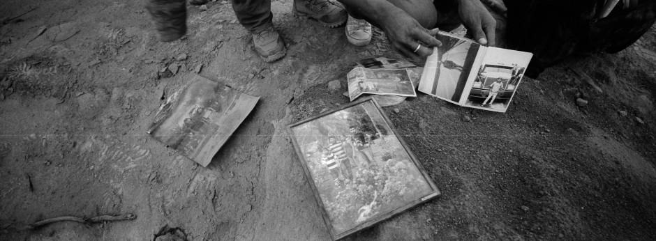 Bewohner blättern in Familienfotos, gefunden außerhalb eines zerstörten Hauses in San Miguel Los Lotes.
