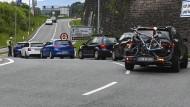 Ein Polizist hält Autos vor einer Autobahnauffahrt bei Innsbruck an.