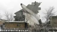 Das zerstörte Heck eines Frachtflugzeugs vom Typ Boing 747 der Fluggesellschaft ACT ragt nahe des Flughafens Manas in Bischkek (Kirgistan) aus den Trümmern eines Hauses.