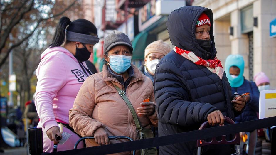 Mehrere Menschen stehen in New York vor einer Essensausgabe Schlange.