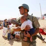 Flüchtlinge an der syrischen Grenze nahe Suruc: Ein türkischer Soldat hält Ausschau nach der Mutter dieses Babys